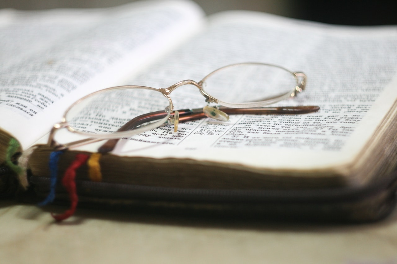 Open Bible with glasses sitting on top of it, commentary reviews