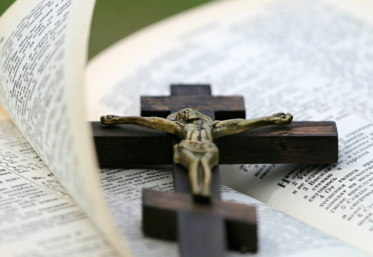 Open Bible with cross laying on it, Why does Jesus bless the persecuted?